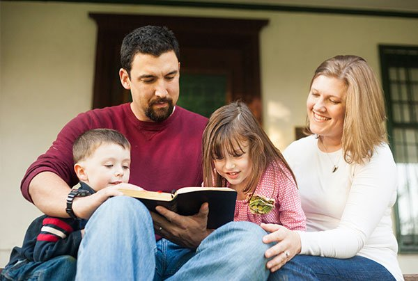 Parents read the bible with their children.