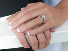 The hands of a married couple with rings showing.