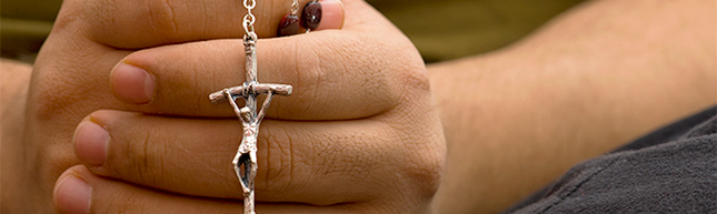 Hands together, holding a rosary.