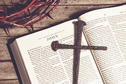 A bible open to the gospel of John, a cross and crown of thorns.